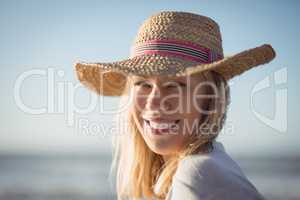 Portrait of happy woman wearing sun hat at beach