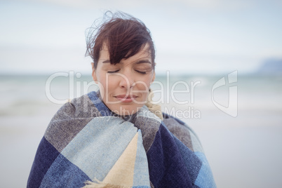 Young woman with eays closed wrapped in blanket during winter