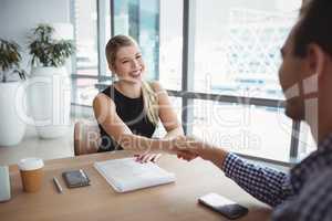 Smiling executives shaking hands at desk