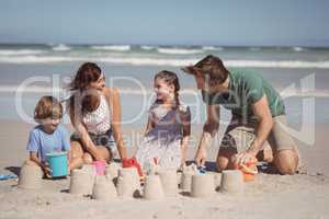 Cheerful family making sand castle at beach