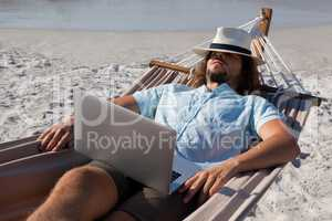Man with laptop relaxing on hammock