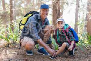 Portrait of father tying shoelace for son in forest