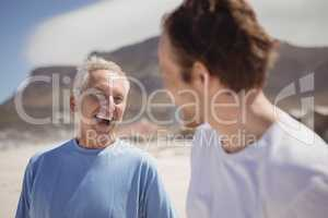 Cheerful senior man with his son standing at beach