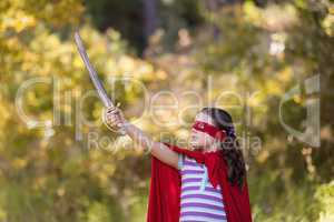 Little girl holding sword while wearing superhero costume