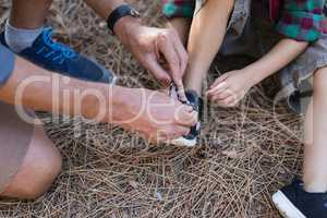High angle view of father tying shoelace for son