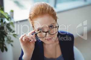 Portrait of executive holding spectacles