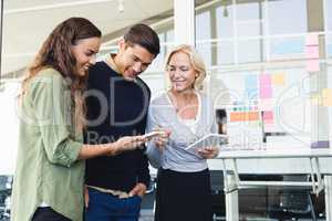 Business people discussing over tablet pc in office