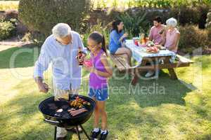 Grandfather and granddaughter preparing barbecue while family having meal