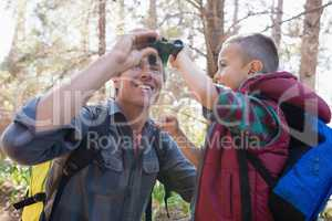 Low angle view of father and son with binoculars