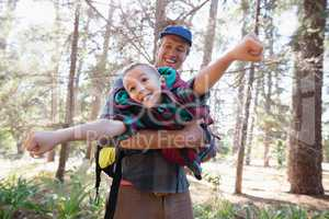 Playful father carrying son in forest
