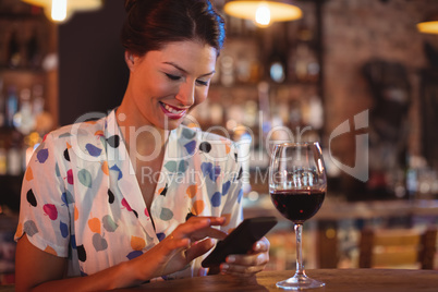 Young woman using mobile phone while having wine