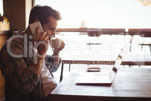 Man talking on mobile phone while having coffee