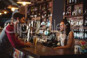 Female bar tender interacting with customer