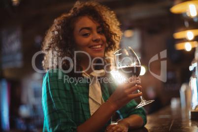Woman having wine at bar counter