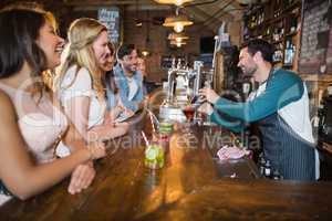 Cheerful bartender interacting with customers while making drink