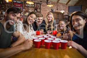 Portrait of smiling friends around disposable cups on table