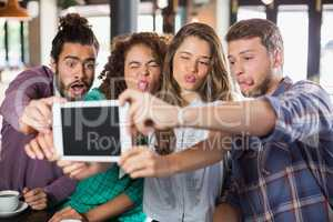 Playful friends taking selfie with digital tablet