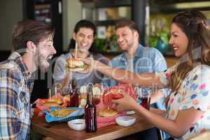 Smiling woman feeding burger to male friend