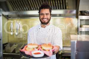 Chef holding burgers in plate at commercial kitchen