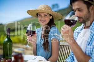 Smiling woman holding wineglass while sitting with man