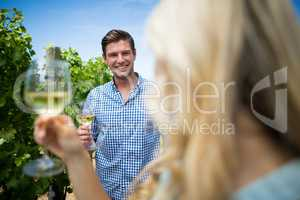 Smiling man looking at woman holding wineglasses