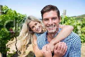 Cheerful couple embracing at vineyard