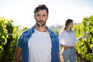 Serious young man standing at vineyard