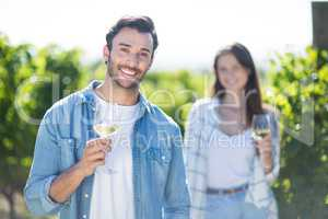 Happy young couple posing with wineglasses at vineyard