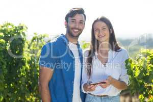 Portrait of young couple holding mobile phone at vineyard