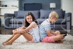 Siblings sitting back to back while boy using digital tablet