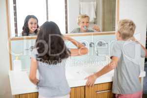 Siblings brushing their teeth in bathroom