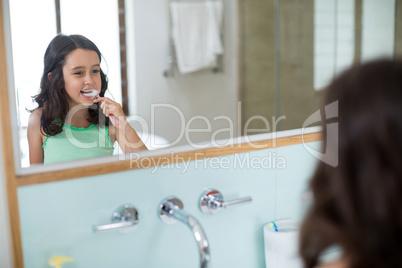 Girl brushing her teeth in bathroom