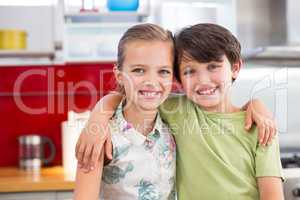 Siblings standing with arm around in kitchen