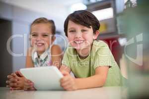 Happy sibling with digital tablet in kitchen