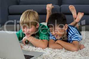 Smiling siblings lying on rug and using laptop in living room