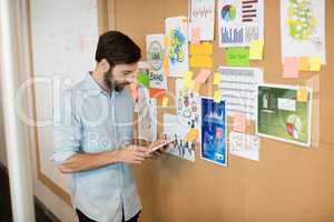 Young businessman using mobile phone by soft board