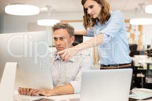 Female colleague assisting businessman working in office