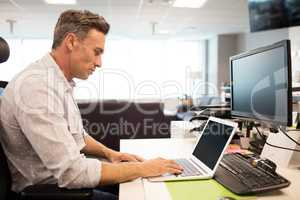 Side view of businessman using laptop in office