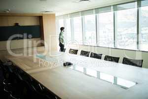 Businessman looking through window in meeting room