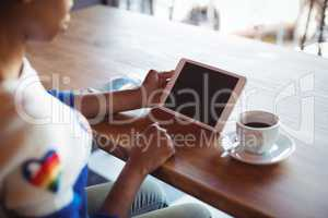 Woman using digital tablet while having coffee