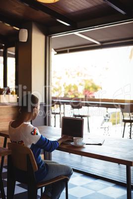 Woman using laptop while having coffee