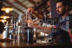 Male bar tender opening a bottle of wine