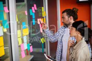 Male and female executives looking at sticky notes