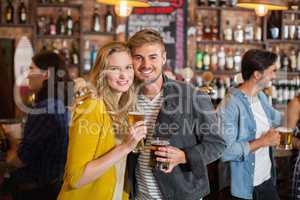 Young friends holding beer glasses in pub