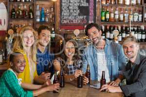 Portrait of cheerful young friends with beer bottles in pub