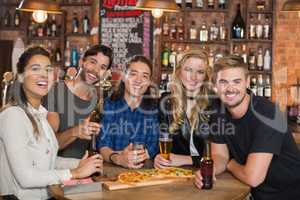 Portrait of happy friends having pizza with beer