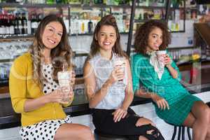 Fashionable female friends having drink in restaurant