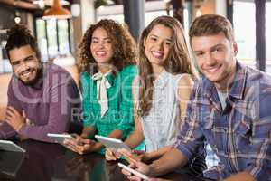 Portrait of friends holding digital tablets in restaurant