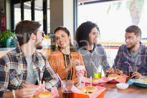 Friends talking while having lunch in restaurant