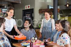 Friends looking at waitress serving food in restaurant